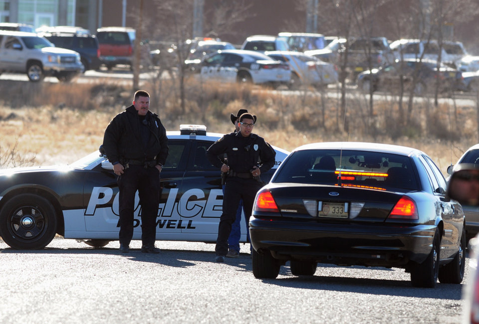 Photo - Law enforcement personnel set up a perimeter following a shooting at Berrendo Middle School in Roswell, Tuesday, Jan. 14, 2014, in Roswell, N.M. A shooter opened fire at the middle school, injuring at least two students before being taken into custody. Roswell police said the school was placed on lockdown, and the suspected shooter was arrested. (AP Photo/Roswell Daily Record, Mark Wilson)