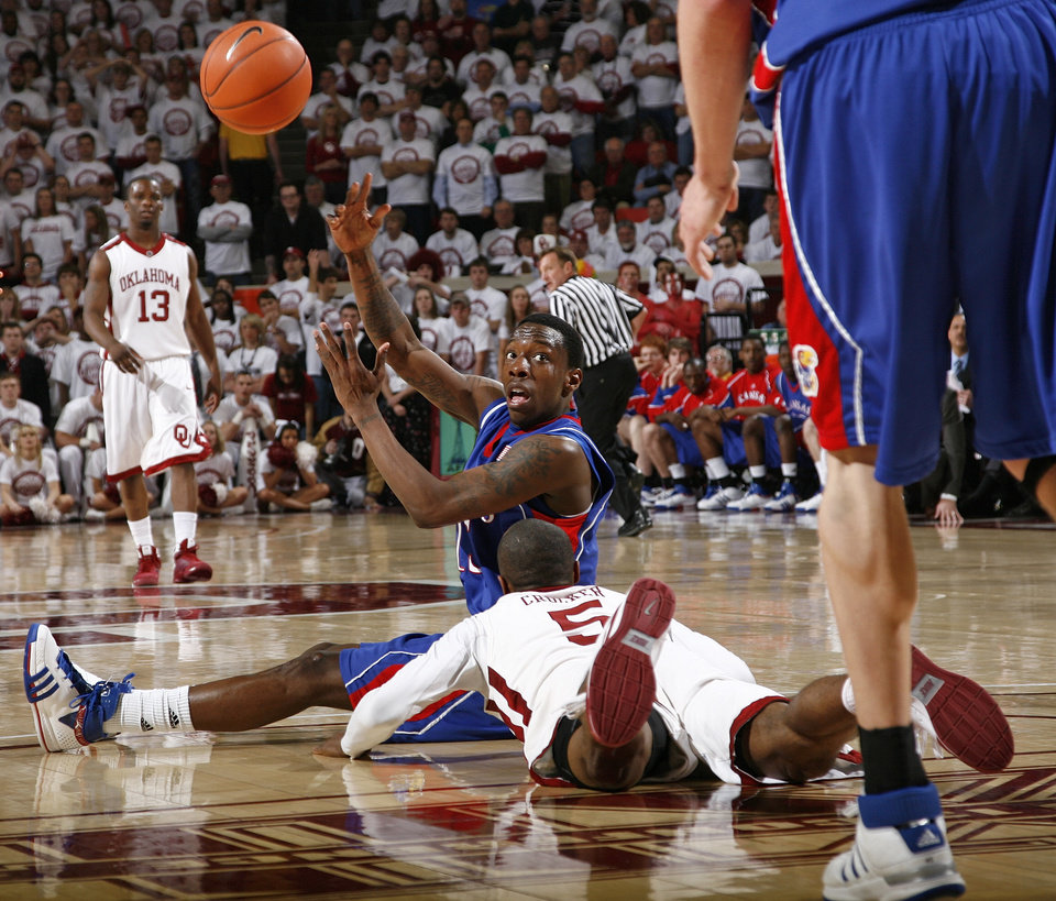 Photo - KU's Tyshawn Taylor (15) tosses the ball to another Jayhawk over OU's Tony Crocker (5) in the second half of the men's college basketball game between Kansas and Oklahoma at the Lloyd Noble Center in Norman, Okla., Monday, February 23, 2009. KU won, 87-78. BY NATE BILLINGS, THE OKLAHOMAN