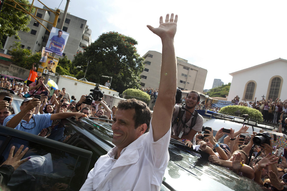 Photo -   Opposition presidential candidate Henrique Capriles waves to supporters as he leaves a polling station after voting in the presidential election in Caracas, Venezuela, Sunday, Oct. 7, 2012. Capriles is running against President Hugo Chavez. (AP Photo/Ramon Espinosa)