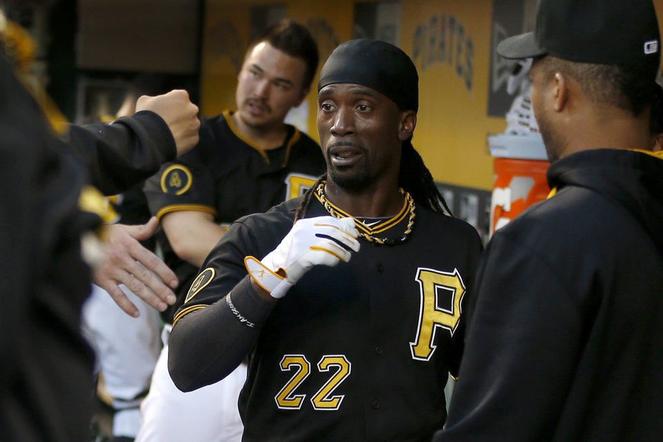 Photo - Pittsburgh Pirates' Andrew McCutchen (22) is greeted by teammates in the dugout after scoring from third when Ike Davis was caught in a rundown long enough for McCutchen to score against the New York Mets in the fourth inning of a baseball game Thursday, June 26, 2014, in Pittsburgh. (AP Photo/Keith Srakocic)