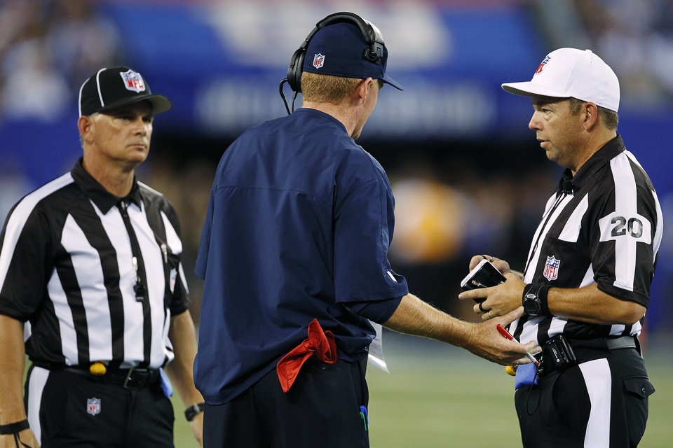Photo -   Dallas Cowboys head coach Jason Garrett, center, argues with referee Jim Core (20) during the first half of an NFL football game against the New York Giants, Wednesday, Sept. 5, 2012, in East Rutherford, N.J. (AP Photo/Julio Cortez)