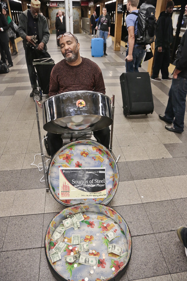 Photo - In this Wednesday, Oct. 9, 2013 photo, Roland Richards closes his eyes as he plays music, from classical to current, on a steel drum for subway riders on the 34th Street subway platform in New York. Richards, who immigrated from Trinidad and brought the indigenous pan music as well, says he is a professional welder by trade.