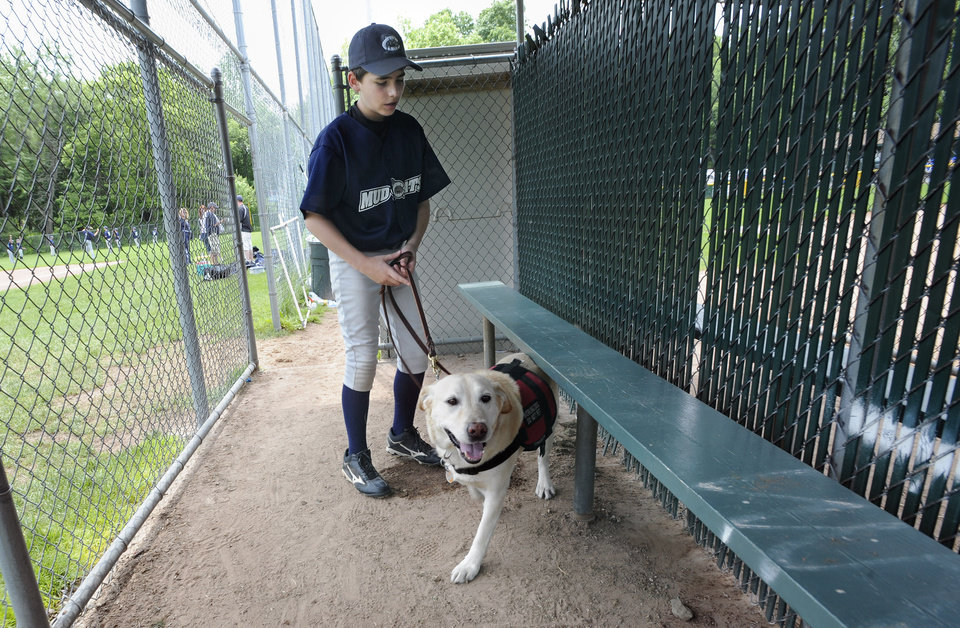 In this Sunday, May 29, 2011 file photo, Jeff Glazer guides his allergy-sniffing dog, Riley, through a dugout of a ball field before his team\'s baseball game in Middlebury, Conn. Riley accompanies Jeff to ensure there are no peanut products or residue that could trigger his life-threatening allergic reactions. (AP Photo/Jessica Hill)
