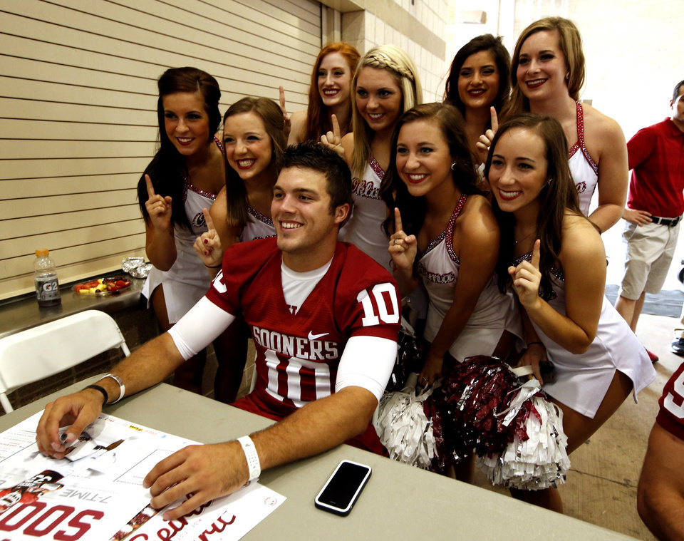 Photo - Sooner cheer squad members pose with quarterback Blake Bell during fan appreciation day for the University of Oklahoma Sooner (OU) football team at Gaylord Family-Oklahoma Memorial Stadium in Norman, Okla., on Saturday, Aug. 3, 2013. Photo by Steve Sisney, The Oklahoman