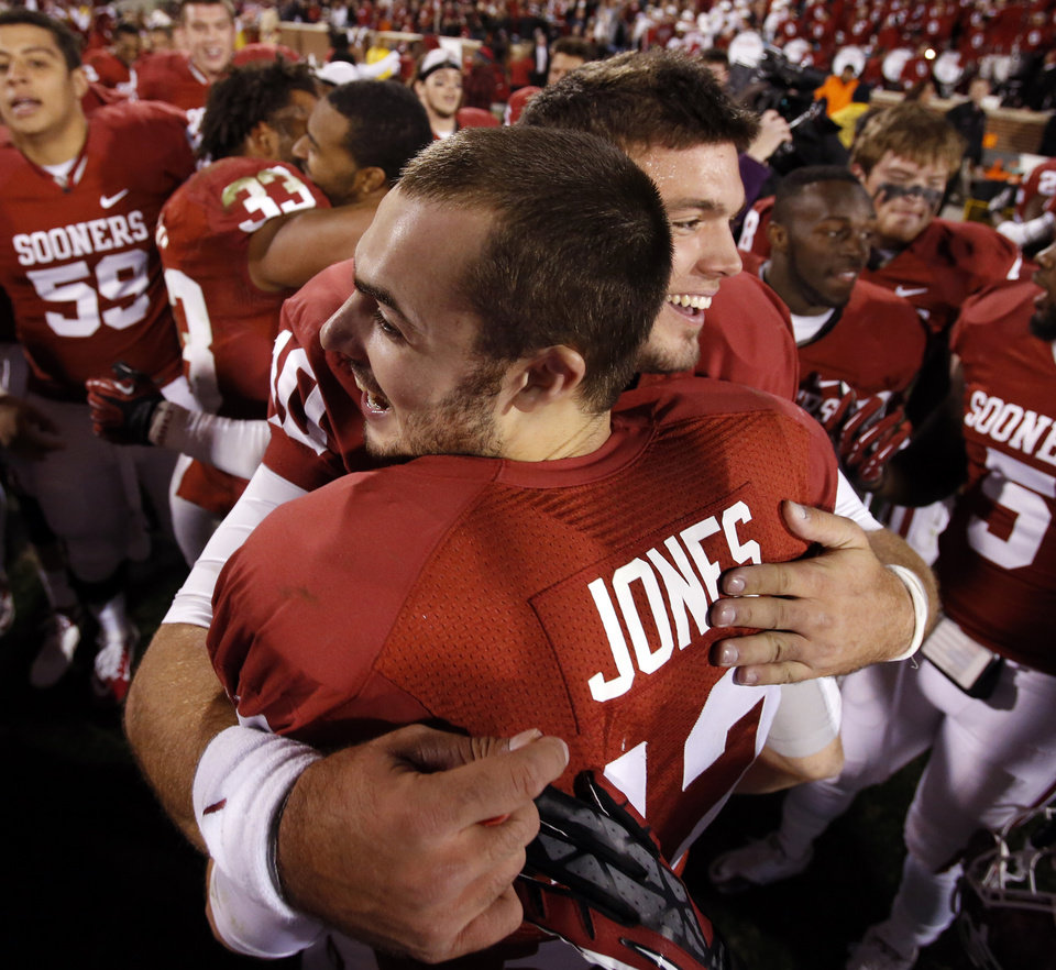 Photo - Sooner quarterbacks Landry Jones (12) and Blake Bell (10) hug after the Bedlam college football game in which  the University of Oklahoma Sooners (OU) defeated the Oklahoma State University Cowboys (OSU) 51-48 in overtime at Gaylord Family-Oklahoma Memorial Stadium in Norman, Okla., Saturday, Nov. 24, 2012. Photo by Steve Sisney, The Oklahoman