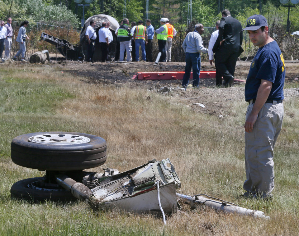 Photo - A National Transportation Safety Board official looks at a piece of the landing gear at the scene Monday, June 2, 2014, in Bedford, Mass., where a plane plunged down an embankment and erupted in flames during a takeoff attempt at Hanscom Field on Saturday night. Lewis Katz, co-owner of The Philadelphia Inquirer, and six other people died in the crash. (AP Photo/Boston Herald, Mark Garfinkel, Pool)