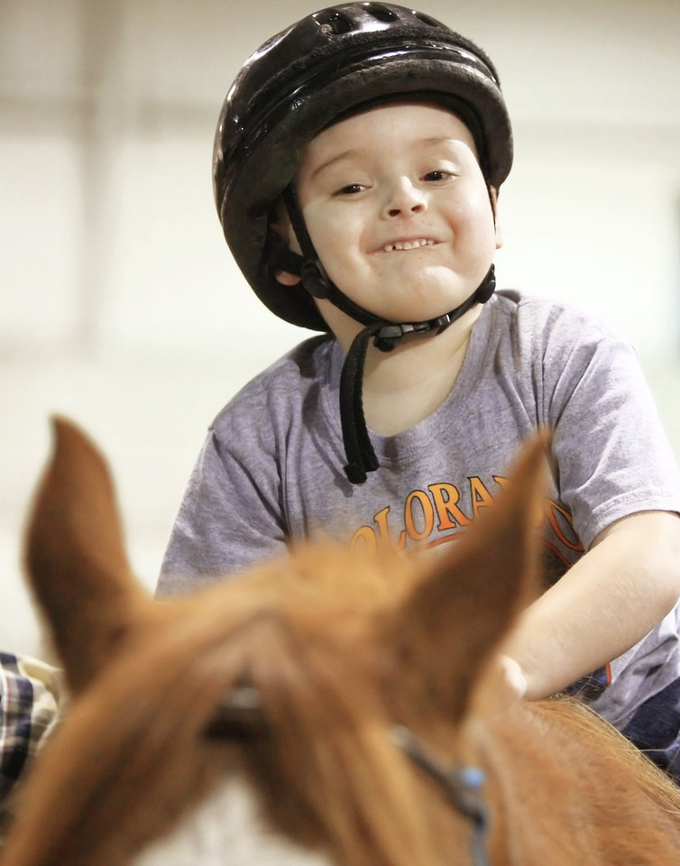Photo - Jacob Enyart, of Colcord, 7, rides Jake, one of the EquiSpirit Riding Academy horses, at NEO A&M Arena.  Photo by STEPHEN HOLMAN, TULSA WORLD