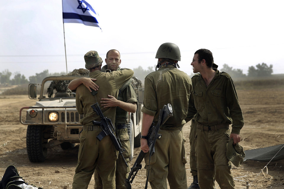 Photo - Israeli reserve soldiers greet each other after a few weeks apart near the Israel Gaza border, Monday, July 28, 2014. A truce between Israel and Hamas militants in Gaza remained elusive as diplomats sought to end the fighting at the start of the Eid al-Fitr holiday, marking the end of the Muslim holy month of Ramadan. (AP Photo/Tsafrir Abayov)