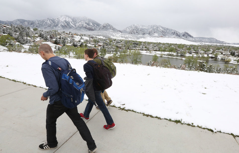 Photo - High school students walk past fresh snow from the fringe of a major spring snowstorm in the nearby mountains, in Boulder, Colo., on Monday, May 12, 2014. A spring storm has brought up to 3 feet of snow to the Rockies and severe thunderstorms and tornadoes to the Midwest. In Colorado, the snow that began falling on Mother's Day caused some power outages as it weighed down newly greening trees. (AP Photo/Brennan Linsley)