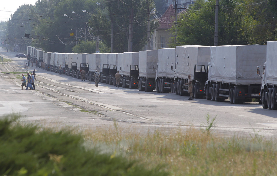 Photo - Drivers of the first trucks of the Russian aid convoy are parked in the city of Luhansk, eastern Ukraine, Friday, Aug. 22, 2014. The first trucks in a Russian aid convoy crossed into eastern Ukraine on Friday, after more than a week's delay. (AP Photo/Sergei Grits)