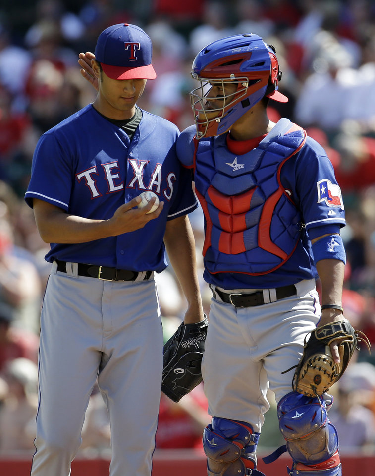 Photo - Texas Rangers catcher Robinson Chirinos,right,  talks to Yu Darvish during the second inning of an exhibition spring training baseball game against the Los Angeles Angels Tuesday, March 4, 2014, in Tempe, Ariz. (AP Photo/Morry Gash)