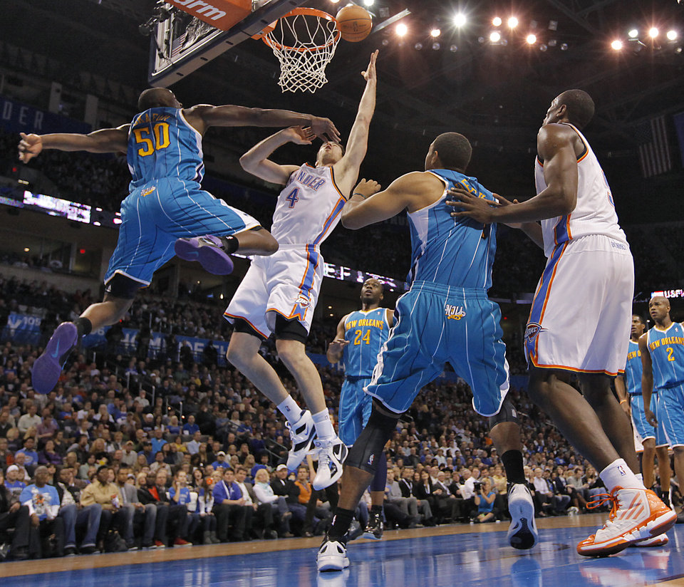 Photo - Oklahoma City Thunder power forward Nick Collison (4) puts up a shot past New Orleans Hornets center Emeka Okafor (50) during the NBA basketball game between the Oklahoma City Thunder and the New Orleans Hornets at the Chesapeake Energy Arena on Wednesday, Jan. 25, 2012, in Oklahoma City, Okla. Photo by Chris Landsberger, The Oklahoman
