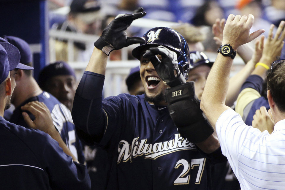 Photo -   Milwaukee Brewers' Carlos Gomez celebrates in the dugout after his second-inning, two-run home run during a baseball game against the Miami Marlins in Miami, Monday, Sept. 3, 2012. (AP Photo/J Pat Carter)