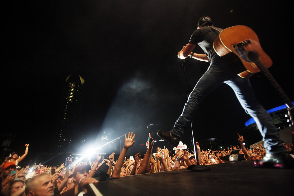 Photo - Country artist Dierks Bentley sings on a runway as fans reach towards him while he performs the headlining set at OKC Fest in downtown Oklahoma City on Friday, June 27, 2014. OKC Fest is a new two day country music festival with multiple stages downtown. Photos by KT King/The Oklahoman
