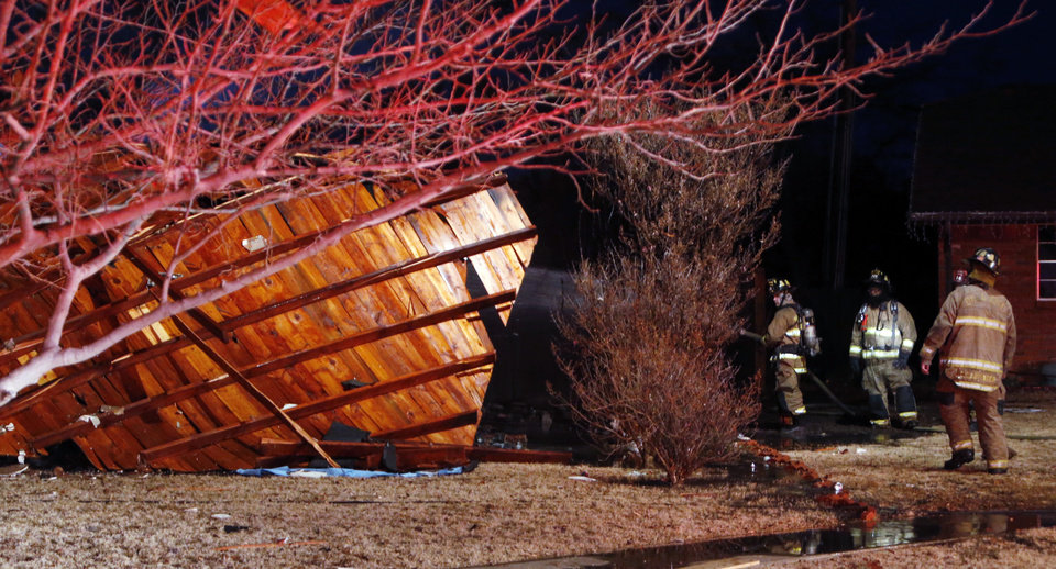 Photo - Firemen spray water on the remains of a house destroyed by a natural gas explosion near SW 92nd and Fairview on Thursday, Jan. 3, 2013  in Oklahoma City, Okla. The roof is at left. Photo by Steve Sisney, The Oklahoman
