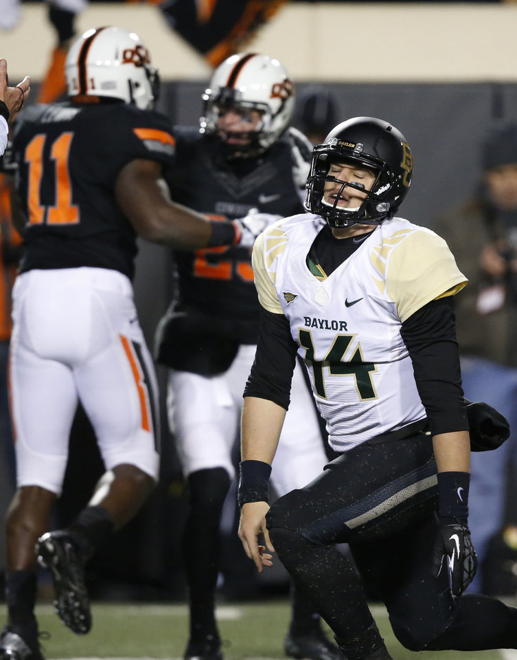 Photo - Baylor quarterback Bryce Petty (14) gets up as Oklahoma State defenders Shaun Lewis (11) and Zack Craig (23) celebrate a sack of Petty in the second quarter of an NCAA college football game in Stillwater, Okla., Saturday, Nov. 23, 2013. (AP Photo/Sue Ogrocki)