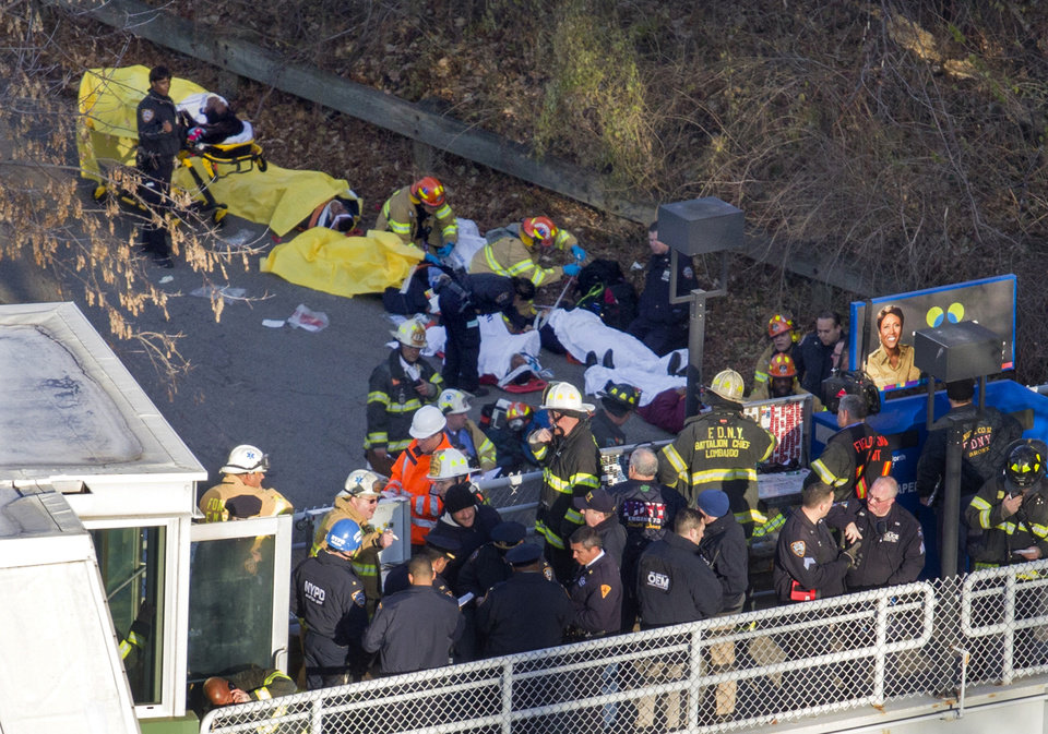 Photo - Injured people are tended to by first responders near the site of the derailment of a Metro-North passenger train in the Bronx borough of New York, Sunday, Dec. 1, 2013. The train derailed on a curved section of track in the Bronx on Sunday morning, coming to rest just inches from the water and causing multiple fatalities and dozens of injuries, authorities said. Metropolitan Transportation Authority police say the train derailed near the Spuyten Duyvil station. (AP Photo/Craig Ruttle)