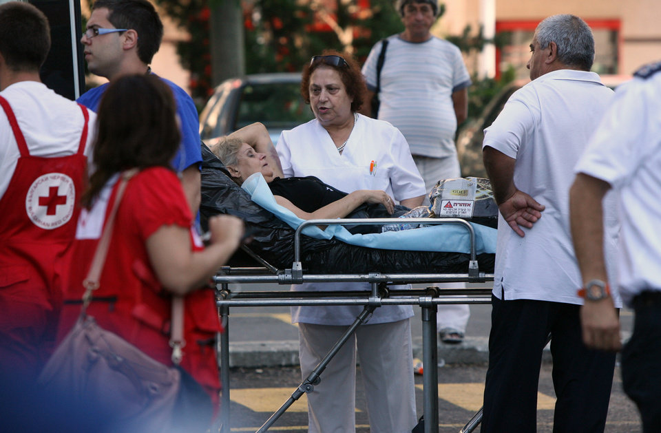 Photo -   An unidentified injured Israeli tourist is helped as she leaves a hospital in the city of Burgas, Bulgaria, Thursday, July 19, 2012. A daytime bombing that killed eight people and injured dozens on a bus full of Israeli tourists was most likely a suicide attack, Bulgaria's interior minister said Thursday. He said the suspected attacker was carrying a Michigan driver's license that was being sent to the FBI for authentication. (AP Photo/Impact Press Group)