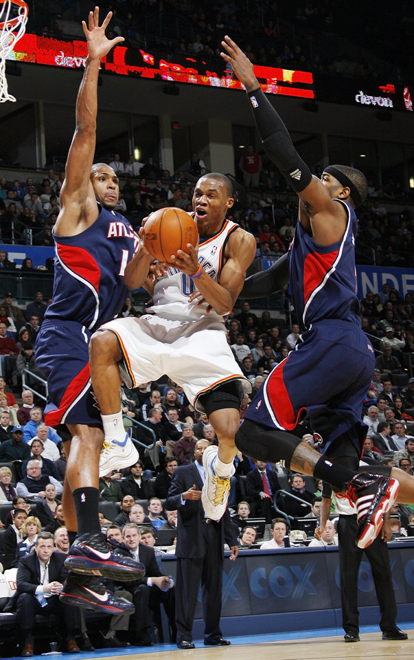 Photo - Oklahoma City's Russell Westbrook (0) moves to the hoop between Al Horford (15), left, and Josh Smith (5) of Atlanta during the NBA basketball game between the Atlanta Hawks and the Oklahoma City Thunder at the Ford Center in Oklahoma City, Tuesday, February 2, 2010. The Thunder won, 106-99. Photo by Nate Billings, The Oklahoman ORG XMIT: KOD