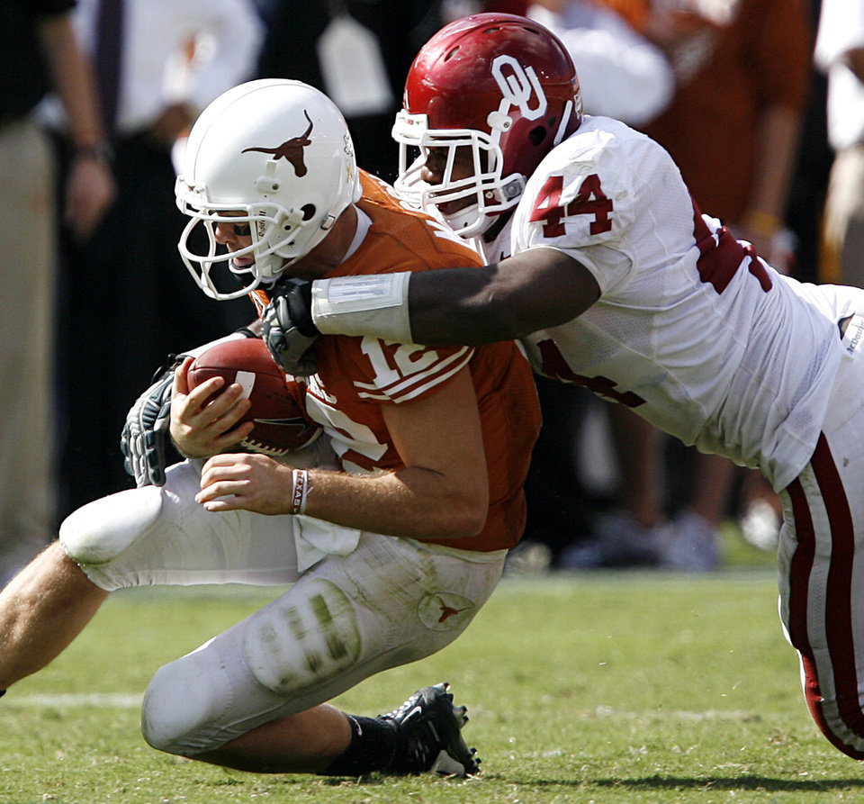 Photo - Oklahoma's Jeremy Beal (44) brings down Texas' Colt McCoy (12) during the Red River Rivalry college football game between the University of Oklahoma Sooners (OU) and the University of Texas Longhorns (UT) at the Cotton Bowl in Dallas, Texas, Saturday, Oct. 17, 2009. Photo by Chris Landsberger, The Oklahoman