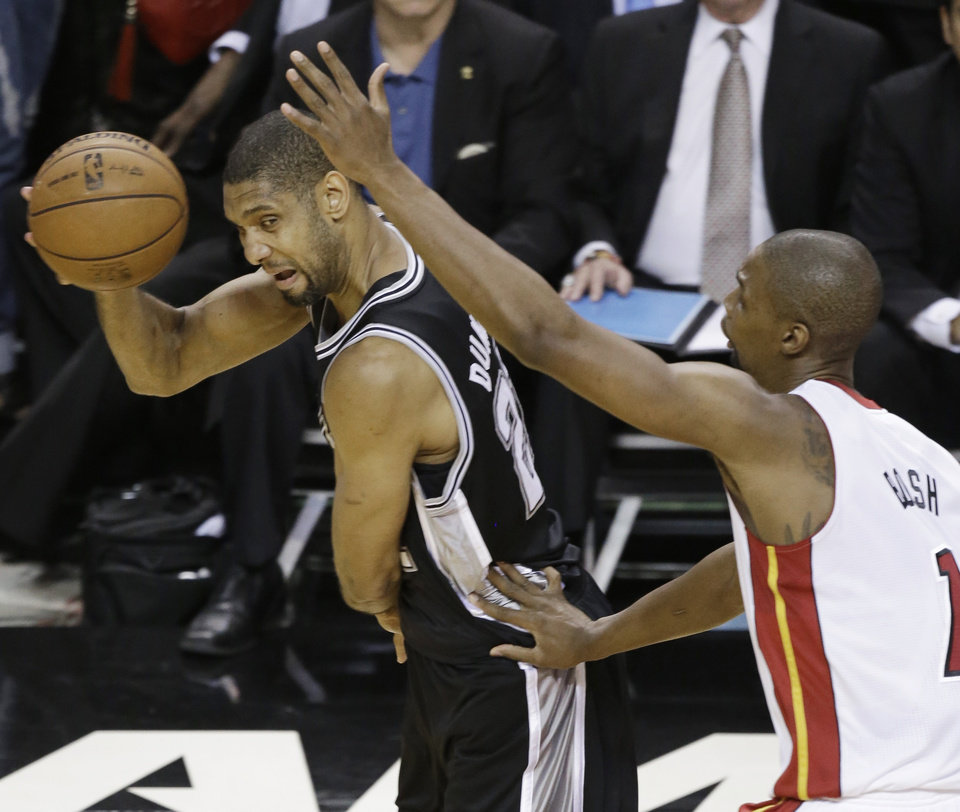 Photo - San Antonio Spurs' Tim Duncan (21) and the Miami Heat's Chris Bosh (1) work during the first half in Game 7 of the NBA basketball championships, Thursday, June 20, 2013, in Miami. (AP Photo/Wilfredo Lee)
