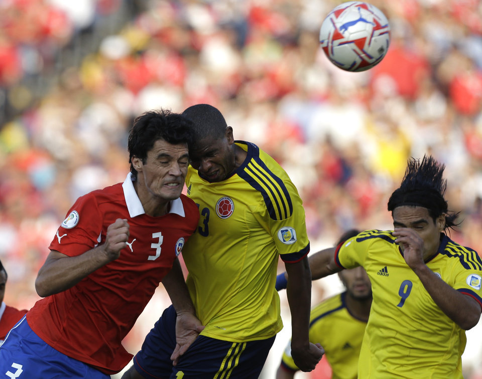 Photo -   Chile's Marcos Gonzalez, left, fights for the ball with Colombia's Edwin Valencia, center, and Falcao Garcia during a World Cup 2014 qualifying soccer game in Santiago, Chile, Tuesday, Sept. 11, 2012. (AP Photo/Eduardo Di Baia)