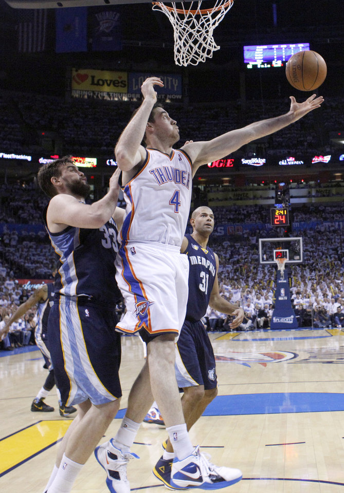 Photo - Oklahoma City's Nick Collison (4) grabs a rebound over Marc Gasol (33) of Memphisduring game five of the Western Conference semifinals between the Memphis Grizzlies and the Oklahoma City Thunder in the NBA basketball playoffs at Oklahoma City Arena in Oklahoma City, Wednesday, May 11, 2011. Photo by Sarah Phipps, The Oklahoman