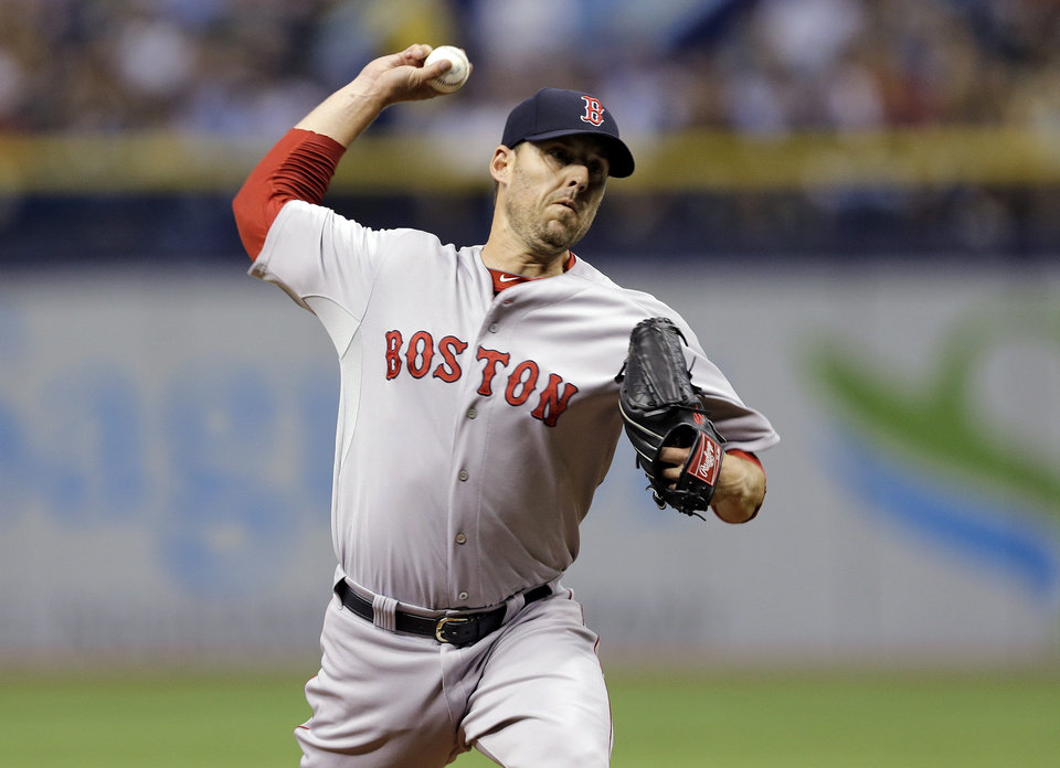 Photo - Boston Red Sox starting pitcher John Lackey delivers to the Tampa Bay Rays during the first inning of a baseball game Saturday, July 26, 2014, in St. Petersburg, Fla. (AP Photo/Chris O'Meara)