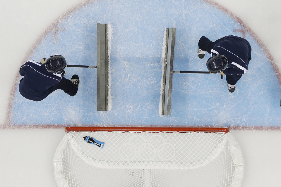 Photo - Volunteers refresh the ice during a break in the action at the 2014 Winter Olympics women's ice hockey game between Japan and Germany at Shayba Arena, Thursday, Feb. 13, 2014, in Sochi, Russia. (AP Photo/Matt Slocum)