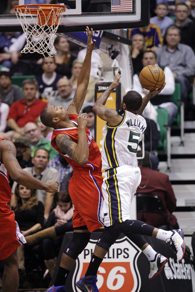 Utah Jazz point guard Mo Williams (5) shoots as Los Angeles Clippers forward Caron Butler defends in the second quarter of an NBA basketball game, Monday, Dec. 3, 2012, in Salt Lake City. (AP Photo/Rick Bowmer)