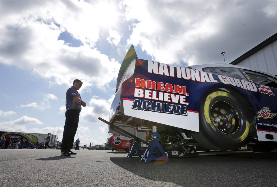 Photo - A crew member stands near the race car of Dale Earnhardt Jr. in the garage area during practice Friday Aug. 2, 2013, for Sunday's NASCAR Sprint Cup Series auto race in Long Pond, Pa. (AP Photo/Mel Evans)