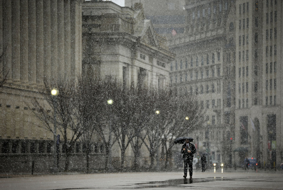 Photo - A pedestrian walks down Pennsylvania Ave near the White House in Washington, Wednesday, March 6, 2013. Schools, businesses and the federal government closed in anticipation of a snow storm that could blanket the region. (AP Photo/Pablo Martinez Monsivais)