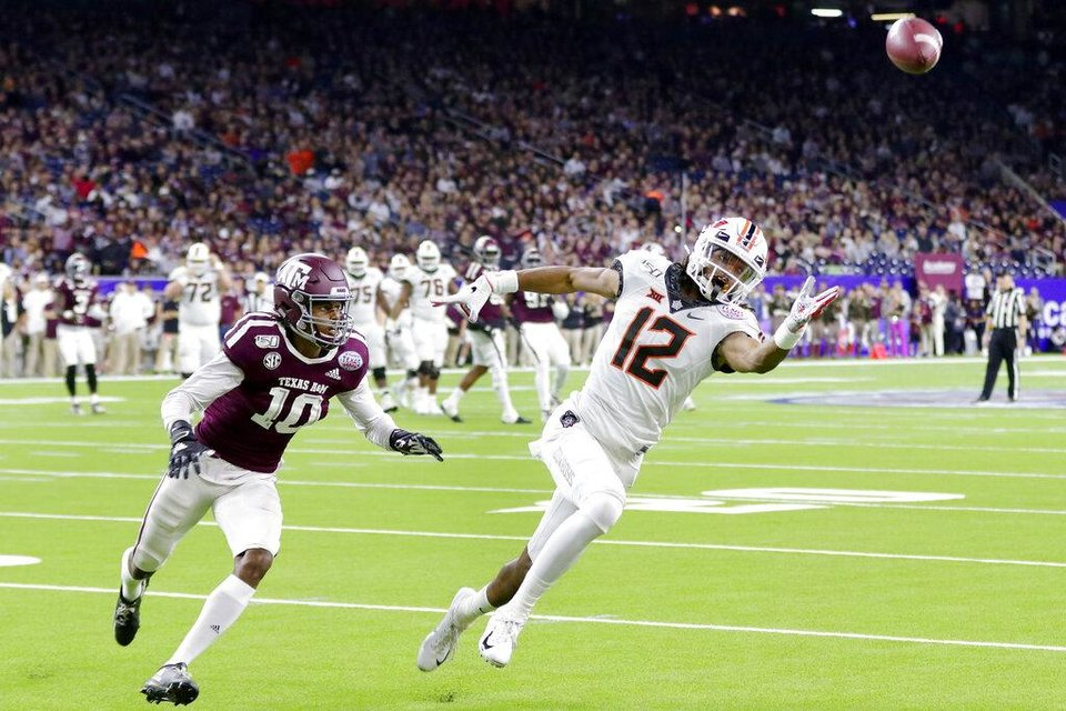 Photo - Oklahoma State wide receiver Jordan McCray (12) reaches for an overthrown pass in front of Texas A&M defensive back Myles Jones (10) during the first half of the Texas Bowl NCAA college football game Friday, Dec. 27, 2019, in Houston. (AP Photo/Michael Wyke)