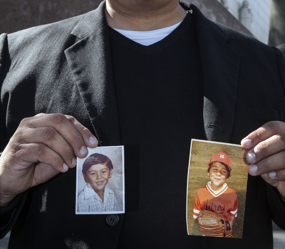 Photo - Michael Duran, a plaintiff in a sex abuse settlement with the Roman Catholic Archdiocese of Los Angeles, holds up pictures of himself when he was a child during a news conference to announce details of a nearly $10 million settlement of their lawsuits against the Archdiocese of Los Angeles Thursday, March 14, 2013. Duran was molested by ex-priest Michael Baker, who is now in jail after pleading guilty pleaded to a dozen sex charges. The U.S. church's challenges include recovering from the clergy sexual abuse scandal, which has resulted in the bankruptcies of prominent archdioceses and cost the Church in America an estimated $3 billion in legal settlements. (AP Photo/Damian Dovarganes)