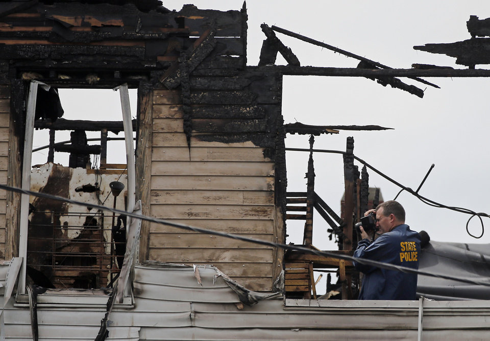 Photo - A state police photographer works on the top floor inside a burned three-story apartment and business building in Lowell, Mass., Thursday, July 10, 2014, where officials said four adults and three children died in a fast-moving pre-dawn fire. (AP Photo/Elise Amendola)