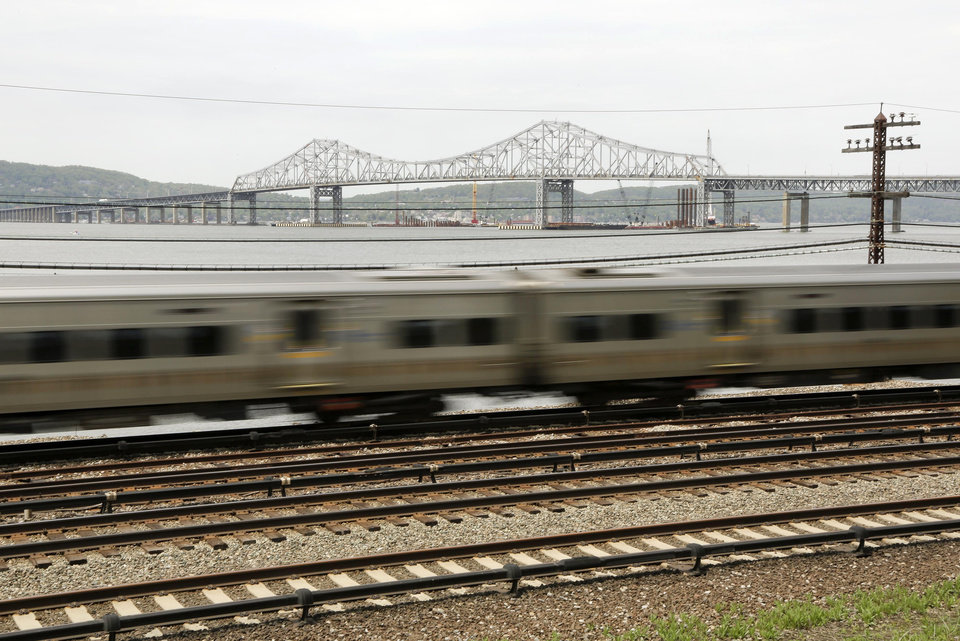 Photo - A Metro North train streaks along the Hudson River just south of the Tappan Zee Bridge, Tuesday, May 13, 2014, in Tarrytown, N.Y. On Wednesday, President Barack Obama plans to speak by the bridge just north of New York City to press his case that a key federal government fund used to pay for the nation's roads, bridges and ports is running dry and that the economy would be damaged if it is not replenished. (AP Photo/Julie Jacobson)