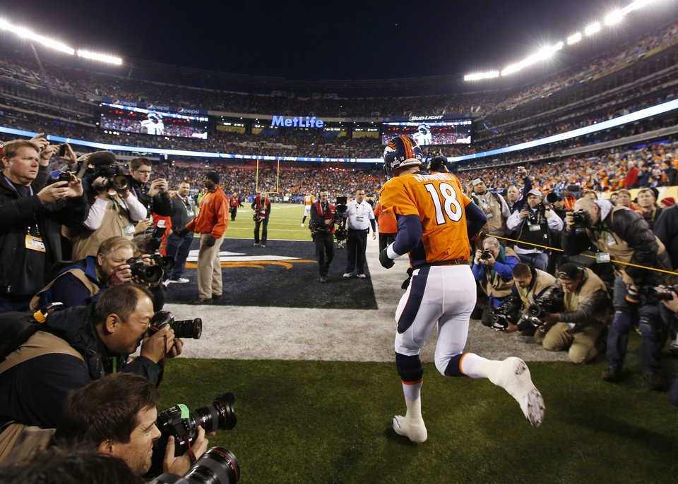 Photo - Denver Broncos quarterback Peyton Manning runs onto the field before the NFL Super Bowl XLVIII football game against the Seattle Seahawks Sunday, Feb. 2, 2014, in East Rutherford, N.J. (AP Photo/Evan Vucci)