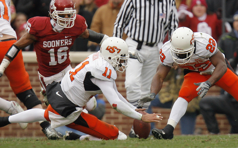 Photo - Oklahoma State's Zac Robinson (11) and Dantrell Savage (22) go after a fumble as Oklahoma's Lewis Baker (16) pursues on the play during the first half of the college football game between the University of Oklahoma Sooners (OU) and the Oklahoma State University Cowboys (OSU) at the Gaylord Family-Memorial Stadium on Saturday, Nov. 24, 2007, in Norman, Okla. 
