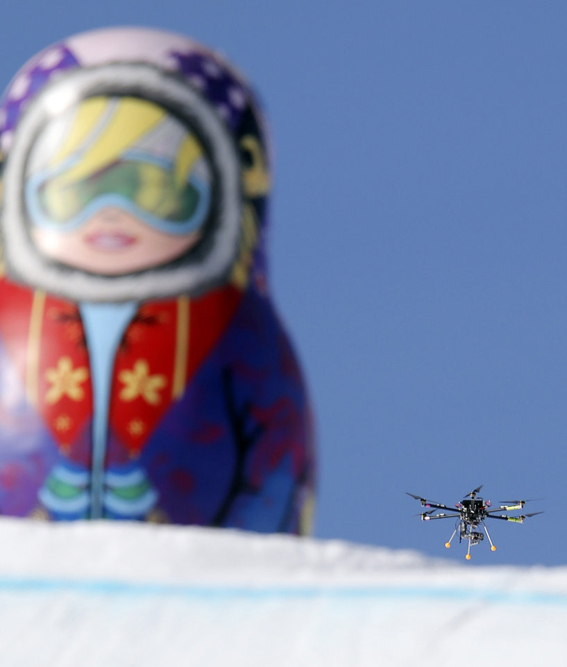 In this Friday Feb. 7 photo, a drone camera  flies about the slopestyle course during a freestyle skiing slopestyle training session at the Rosa Khutor Extreme Park ahead of the 2014 Winter Olympics, Friday, Feb. 7, 2014, in Krasnaya Polyana, Russia. (AP Photo/Sergei Grits)