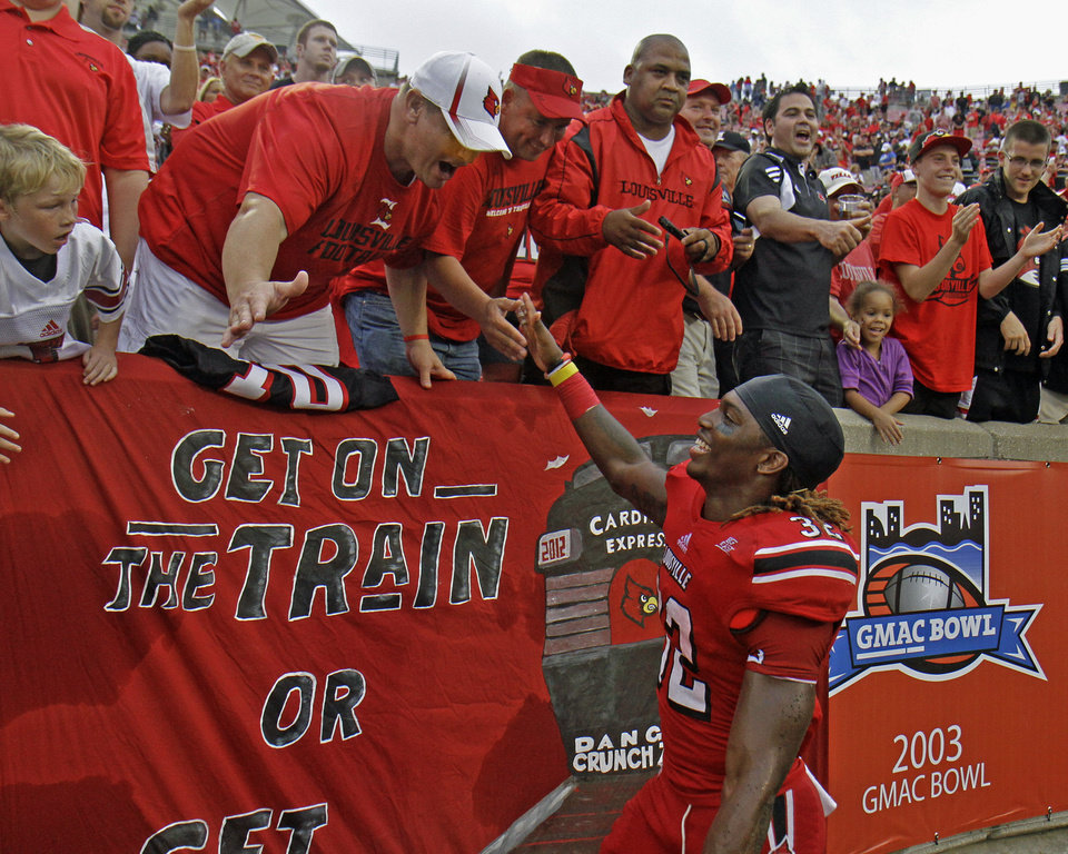 Photo -   Louisville running back Senorise Perry accepts congratulations from fans after helping his team defeat Kentucky 32-14 in their NCAA college football game at Cardinal Stadium in Louisville, Ky., Sunday, Sept. 2, 2012. (AP Photo / Garry Jones)