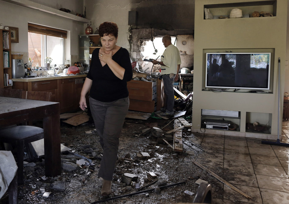 An Israeli woman walks through a damaged house hit by a rocked fired from the Gaza Strip the hit a house near the Israel-Gaza border, Friday, Nov. 16, 2012. Fierce clashes between Israeli forces and Gaza militants are continuing for the third day.(AP Photo/Tsafrir Abayov) ORG XMIT: JRL142