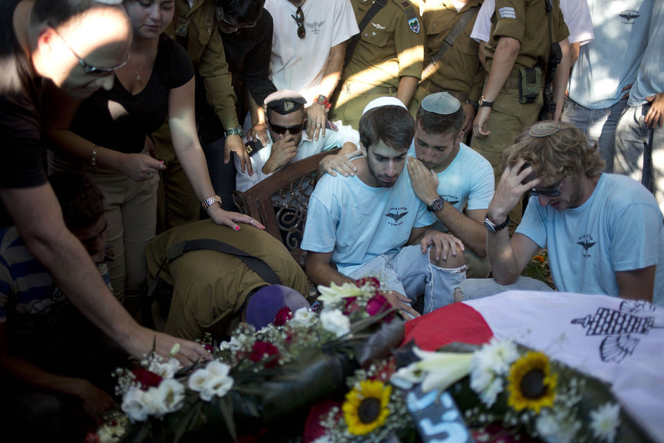 Photo - Family and friends mourn over the grave of Captain Liad Lavi during his funeral in the military cemetery section in the village of Meitar, southern Israel, Monday, July 28, 2014. Lavi, 22, was injured during fighting in Gaza and died from his wounds two day later. (AP Photo/Ariel Schalit)