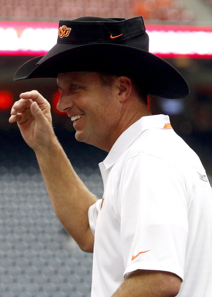 Photo - Oklahoma State head coach Mike Gundy puts his visor on the AdvoCare Texas Kickoff cowboy hat following the AdvoCare Texas Kickoff college football game between the Oklahoma State University Cowboys (OSU) and the Mississippi State University Bulldogs (MSU) at Reliant Stadium in Houston, Saturday, Aug. 31, 2013. Photo by Sarah Phipps, The Oklahoman