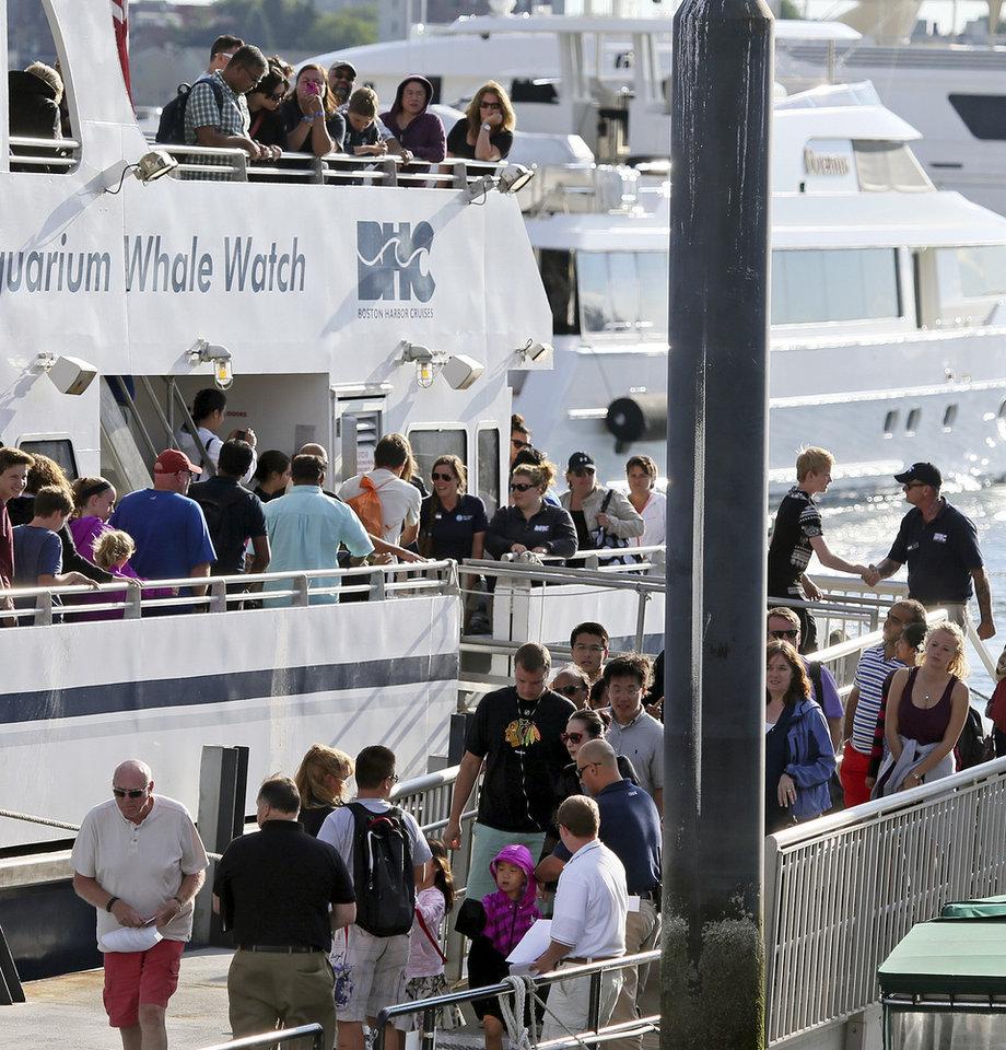 Photo - Passengers disembark the whale watch boat Cetacea Tuesday morning, July 29, 2014 at Long Wharf in Boston. The boat snagged a lobster trap rope during a whale watching excursion about 15 miles off the coast of Massachusetts late Monday, and had to spend a night at sea before divers freed it Tuesday morning. Two Coast Guard cutters remained with the vessel during the night. No injuries were reported to any of the 157 passengers or six crew members. (AP Photo/Boston Herald, Mark Garfinkel)