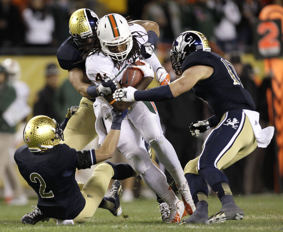 Photo -   Miami tight end Clive Walford, center, advances the ball and is tackled by Notre Dame cornerback Bennett Jackson (2), Manti Te'o, behind, and Zeke Motta (17), during the first half of an NCAA college football game at Soldier Field Saturday, Oct. 6, 2012, in Chicago. (AP Photo/Nam Y. Huh)