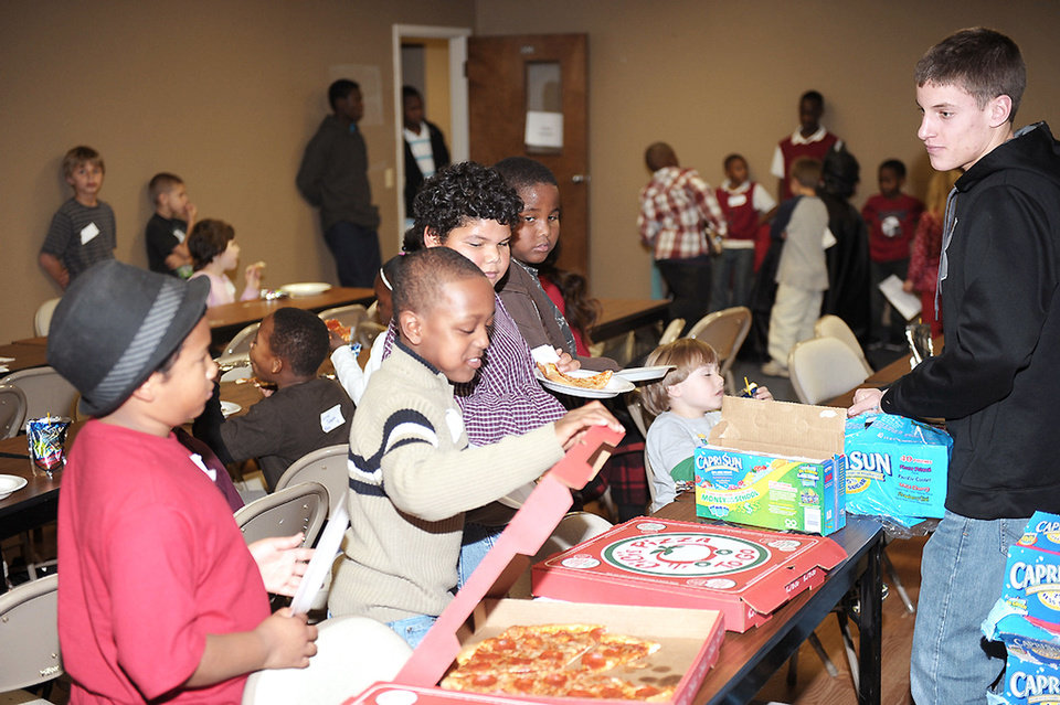 Children get slices of pizza at a Christmas 2011 gathering sponsored by the Single Parent Support Network in partnership with The Cathedral City Reach OKC ministry. Photo provided