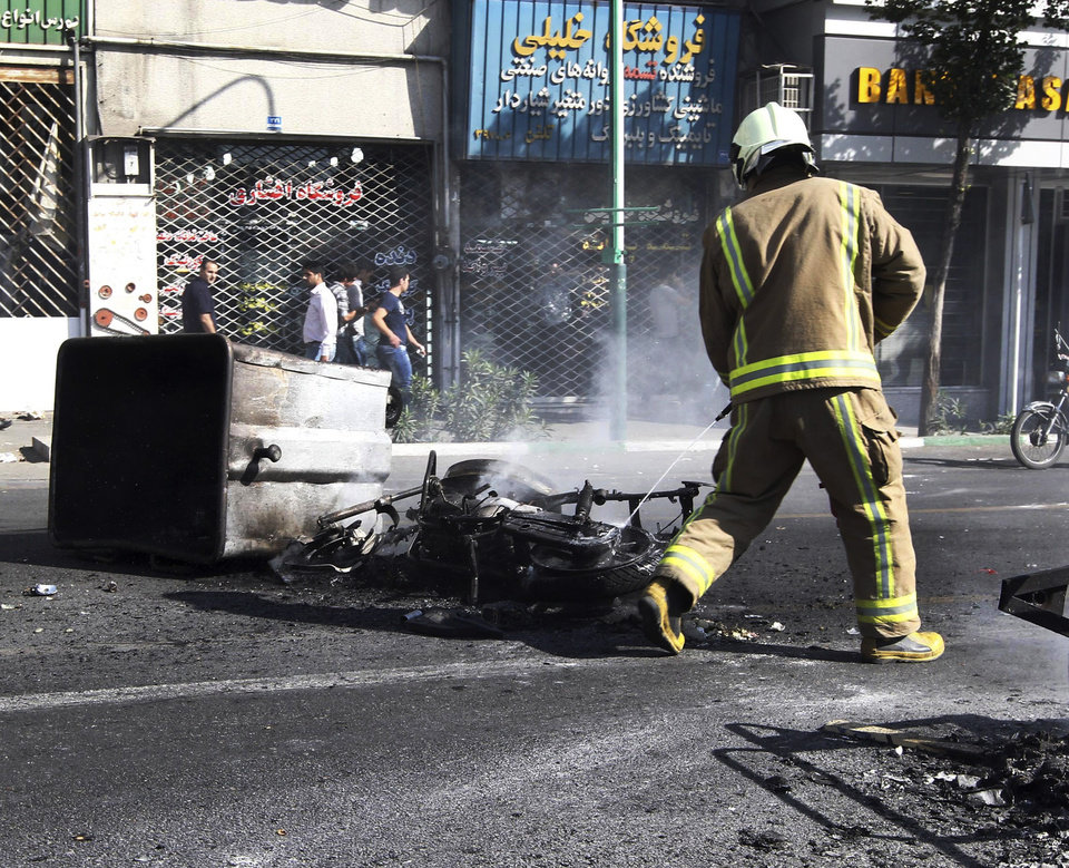 Photo -   In this photo taken by an individual not employed by the Associated Press and obtained by the AP outside Iran, an Iranian fire fighter extinguishes a burned motorcycle in a street in central Tehran, near Tehran's old main bazaar, on Wednesday, Oct. 3, 2012. Police threatened merchants who closed their shops in Tehran's main bazaar and launched crackdowns on sidewalk money changers on Wednesday as part of a push to halt the plunge of Iran's currency, which has shed more than a third its value in less than a week. (AP Photo) EDITORS NOTE AS A RESULT OF AN OFFICIAL IRANIAN GOVERNMENT BAN ON FOREIGN MEDIA COVERING SOME EVENTS IN IRAN, THE AP WAS PREVENTED FROM INDEPENDENT ACCESS TO THIS EVENT.