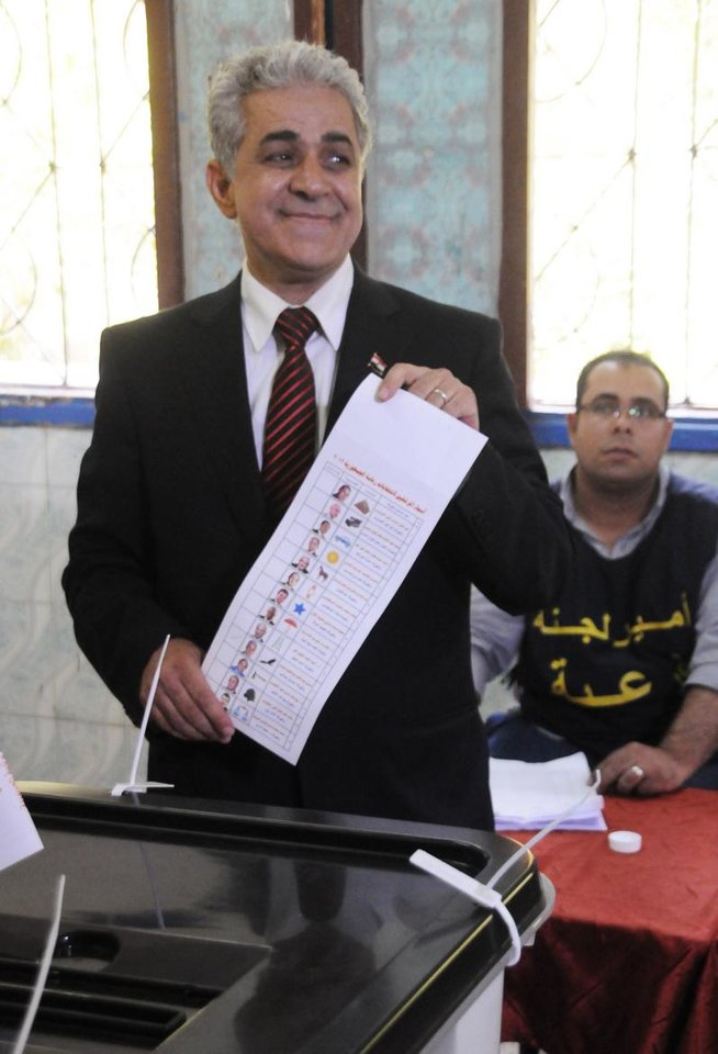 Photo -   Egyptian presidential candidate, Hamdeen Sabahi shows the ballot paper after voting inside a polling station in Cairo, Egypt, Wednesday, May 23, 2012. More than 15 months after autocratic leader Hosni Mubarak's ouster, Egyptians streamed to polling stations Wednesday to freely choose a president for the first time in generations. (AP Photo/Ahmed Hammad)