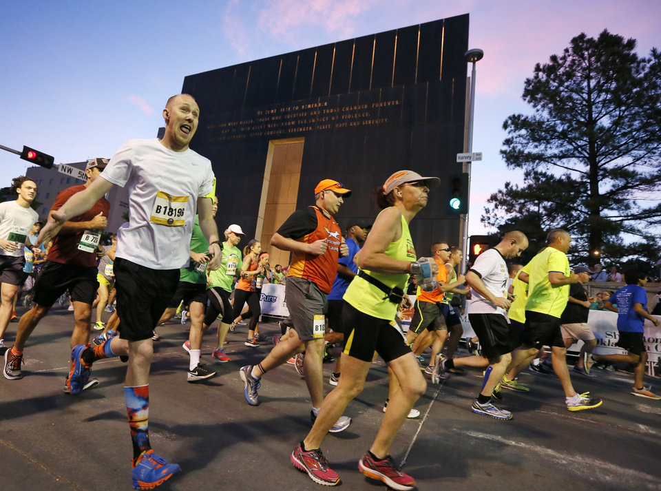 Photo -  Runners on Sunday begin the Oklahoma City Memorial Marathon going south on N Harvey Avenue in downtown Oklahoma City. [Photo by Nate Billings, The Oklahoman]