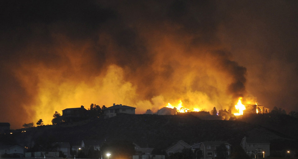 Photo - Houses in the Mountain Shadows area of Colorado Springs, Colorado ignite due to the Waldo Canyon fire on Wednesday, June 26, 2012. (AP Photo/The Gazette, Jerilee Bennett) ORG XMIT: COCOL109